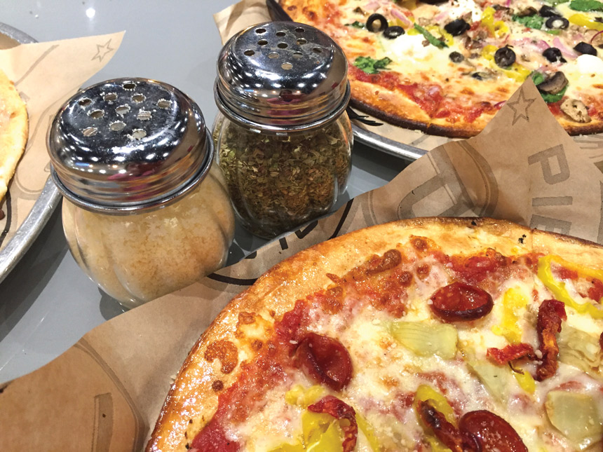 tabletop condiments with pizza